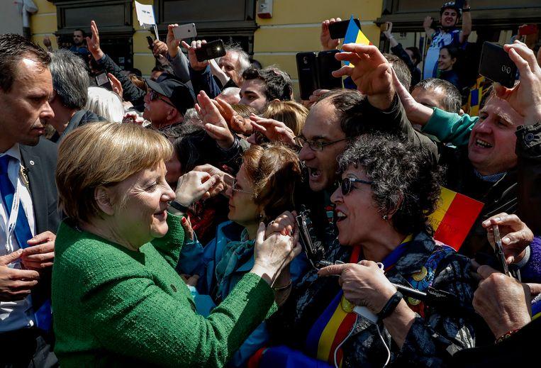 De Duitse bondskanselier Merkel neemt, samen met andere EU-regeringsleiders, spontaan een bad in het publiek dat van afstand de EU-top in het Roemeense Sibiu probeert te volgen.  Beeld EPA
