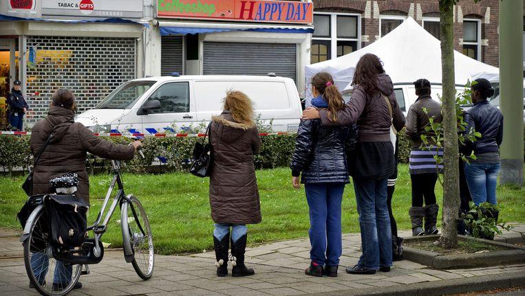 Buurtbewoners kijken naar het onderzoek in de Rotterdamse Boergoenestraat. Beeld EPA