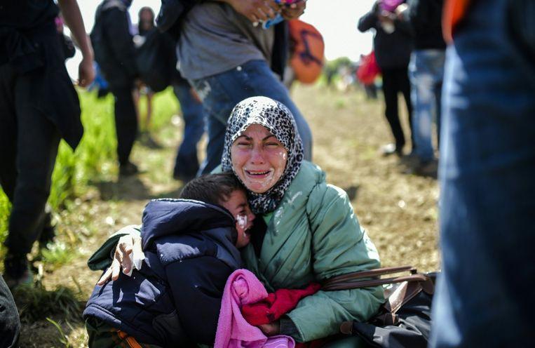 Een vrouw en haar kind huilen nadat ze zijn blootgesteld aan traangas. Beeld null