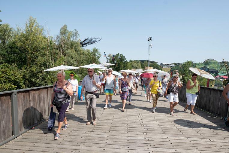 De buurtbewoners van Tomorrowland trotseren met plezier om een kijkje te kunnen nemen op het festivalterrein. De organisatie voorzag parasols en flesjes water.