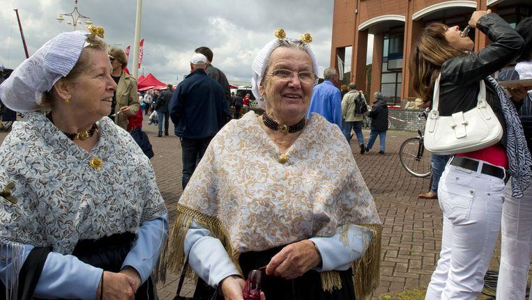 en bezoeker van de traditionele Vlaggetjesdag in Scheveningen proeft zaterdag de nieuwe haring, terwijl twee vrouwen in klederdracht langslopen. Beeld ANP