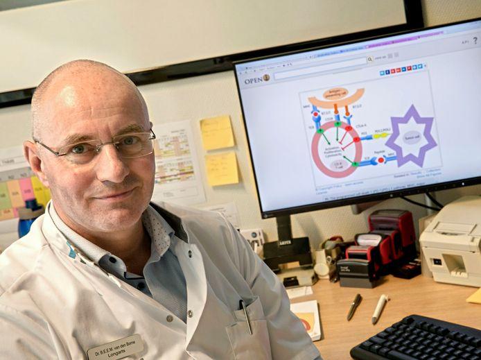 Longarts Ben van den Borne bij een schematisch overzicht van een aanval van witte bloedlichaampjes op een kankercel.