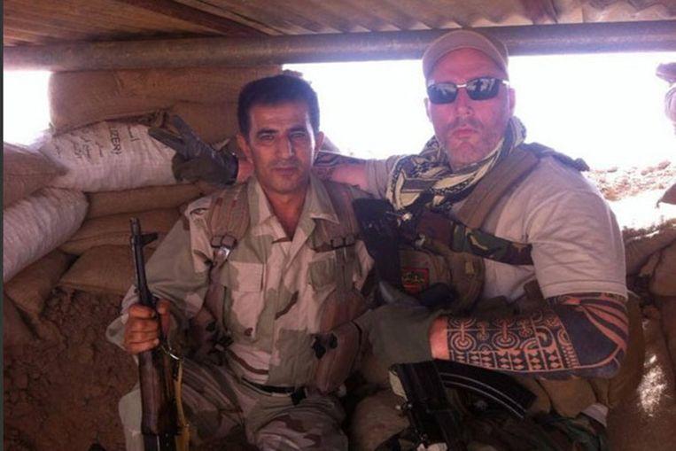 Nederlander Ron (rechts), lid van motorbende No Surrender, poseert naast een Koerdische strijdmakker in een bunker in de buurt van Mosoel.