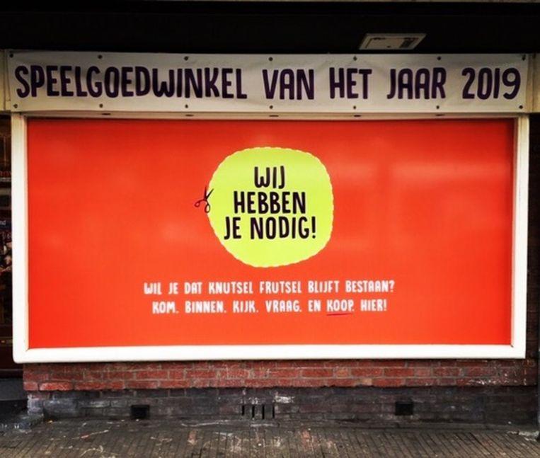 De etalage van de beste speelgoedwinkel van Amsterdam, die al 21 jaar bestaat, is afgeplakt met een noodkreet. Beeld Knutsel Frutsel