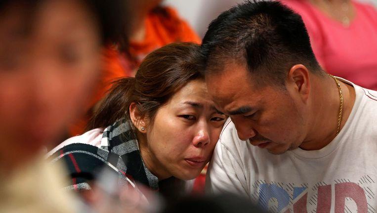 Familieleden van passagiers van AirAsia QZ8501 zoeken troost bij elkaar.