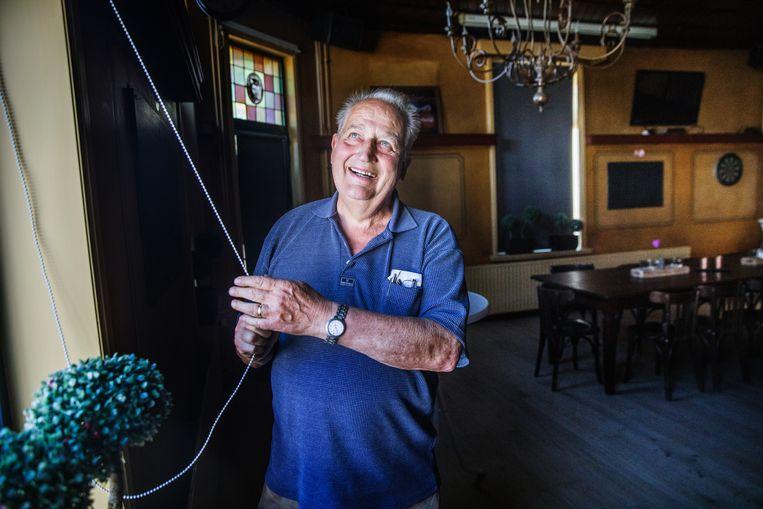 Martin Verberk opent het raam van zijn café Den Bonte Os. Hij mag nog niet open, want het café bevindt zich op Belgische grondgebied.  Beeld Aurélie Geurts