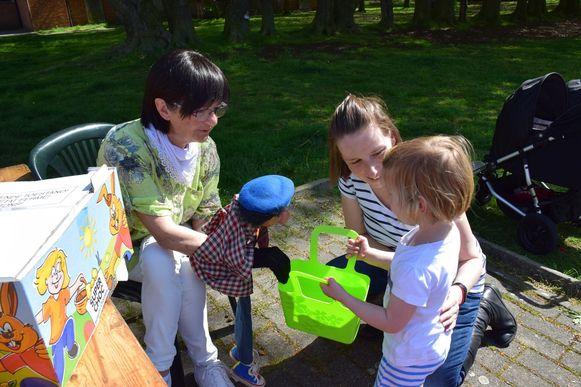 De kinderen tonen hun paaseitjes aan buikspreekster Viviane en haar pop Sloeber.