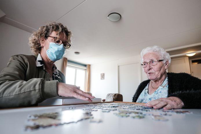 Verpleegkundige Margret Schout en bewoonster Annie Bulsink Brummelman leggen een puzzel in verzorgingstehuis Stegemanhof in Aalten. In dit verzorgingshuis is qua besmettingen nog niks aan de hand, personeel draagt een mondkapje bij langdurig contact.