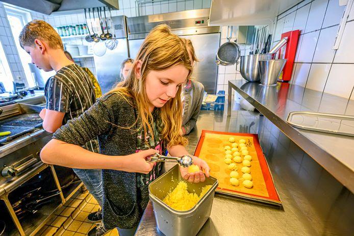 Leerlingen van De Bukehof maken kokosmakronen op de Nationale Horecadag in restaurant d'n Halder in Hoeven.