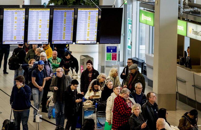 Reizigers op Schiphol kijken naar schermen voor hun reis. Alle vluchten zijn door de westerstorm op Schiphol geannuleerd.
