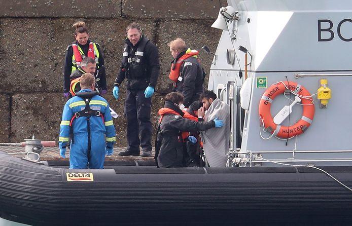 Grensbewakers in het Engelse Dover halen immigranten aan wal die met een kleine boot Het Kanaal zijn overgestoken.