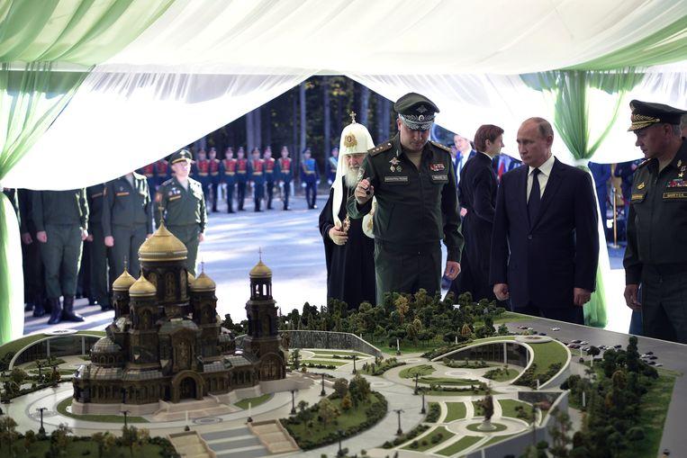 Russische president Vladimir Poetin, vergezeld door minister van defensie Timur Ivanov en patriarch Kirill, bekijkt een miniatuur van de Kerk van de Verlosser op het Bloed  Beeld REUTERS
