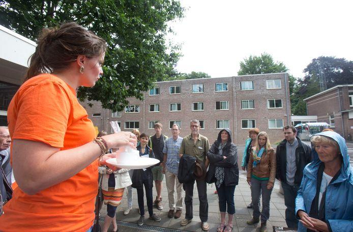 Bezoekers van de open dag van het asielzoekerscentrum De Leemkuil krijgen uitleg over de leefomstandigheden. Op de achtergrond de omstreden nieuwbouw.