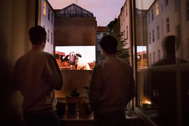 Buren kijken vanaf hun Berlijnse balkon samen naar de film Shaun the sheep.  Beeld Daniel Rosenthal / de Volkskrant