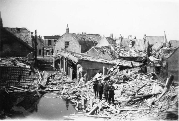 De Lange Ring in Bruinisse na 5 januari 1945, met een bomkrater midden in de straat. Op de voorgrond leden van de Binnenlandsche Strijdkrachten.