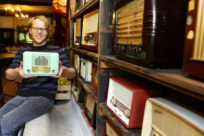 Wouter Blinde (38) in zijn restaurant Oud-Vuren bij de verzameling oude radiotoestellen.