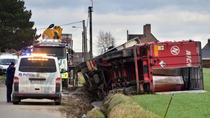 Vrachtwagen sukkelt in gracht tijdens kruisen van andere mastodont langs smalle omleidingsweg