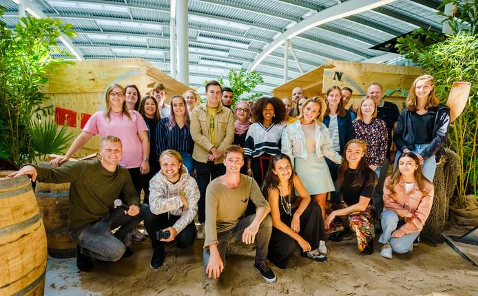 Presentator Kaj Gorgels, Rijk Hofman, Hugo Kennis, Eva Cleven, Eva Koreman, Fien Vermeulen en Yvette Broch poseren samen met fans van het tv-programma tijdens de onthulling van deelnemers aan het nieuwe seizoen van Expeditie Robinson, op Utrecht Centraal.