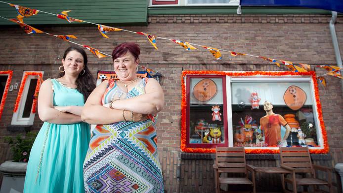 Linda Lancee en dochter Nikki poseren voor hun huis in Ondiep. Achter het raam kijkt 'Wesley'toe.