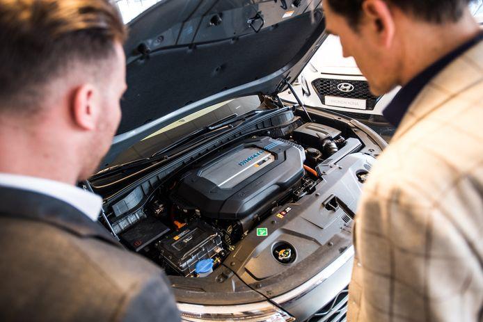 Potentiële kopers werpen een blik onder de motorkap van een Hyundai Nexo, die rijdt op waterstof.