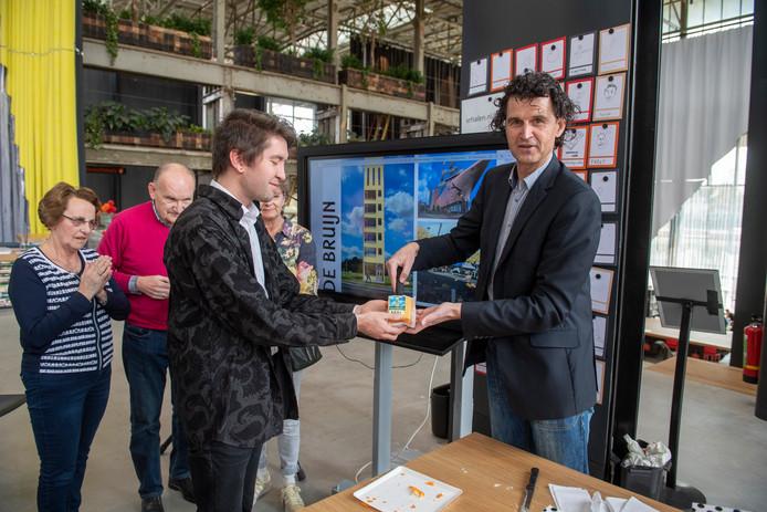 Met een symbolische overhandiging maakt Tim van der Avoird (rechts) bekend dat Ruben de Bruijn (links) het nieuwe leesplankje van Tilburg mag gaan vormgeven.