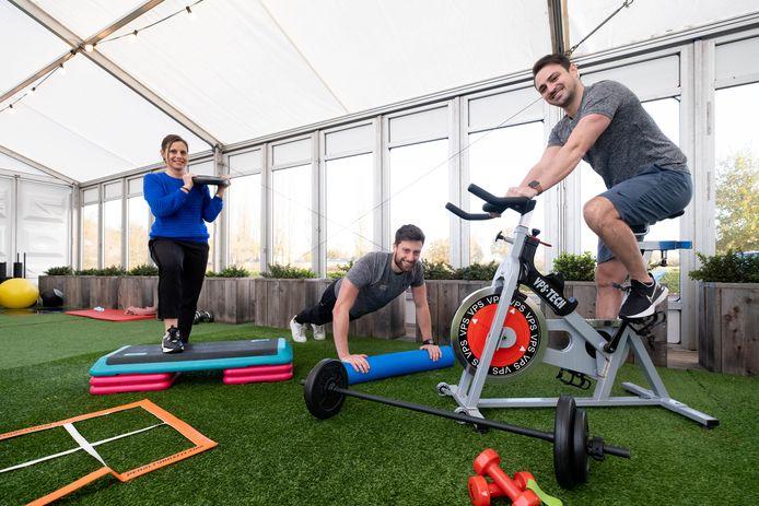 REET Zaakvoerster Ann Van den Rijn met personal trainers Jannis van Doorn en Dries Verrept van Gym Tonic met enkele trainingselementen die ze verhuren