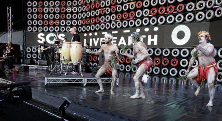 Australische Aboriginals dansen op het podium tijdens het optreden van de Band Blue King Brown. In Sidney is het eerste Live Earth-concert zaterdag begonnen. (AP) Beeld
