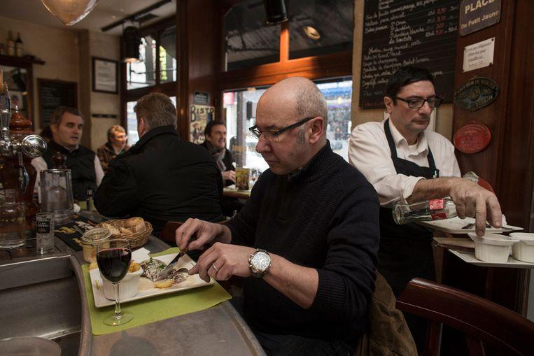 Een gast in restaurant Le Mesturet eet een bavette aan de bar. Achter hem chef Alain Fontaine. Beeld Bart Koetsier