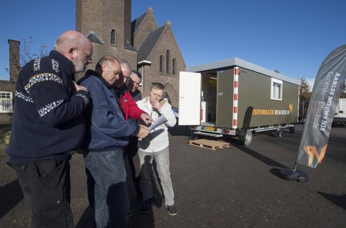 Gebiedsconciërge Boudewijn Albering (2e van links) helpt bezoekers van de Noaber18-keet met kaartmateriaal.