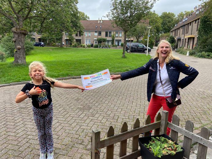 Een dolblije Elize met de cheque van het VriendenFonds van de VriendenLoterij