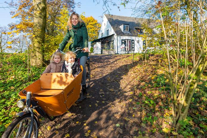 Maartje Oomen met Noor(links) en haar buurmeisje Jasmijn in de bakfiets bij de Hervensedijk. De gemeente wil een trap met fietsgoot, de bewoners een verhard fiets- en voetpad.