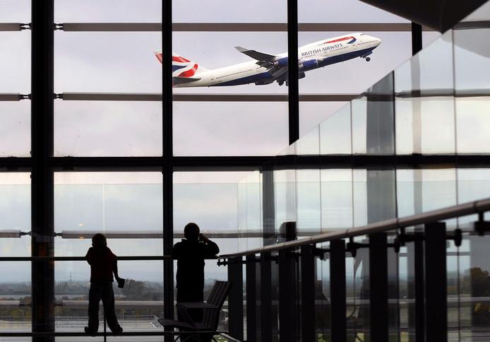 Jeugdige reizigers kijken in Terminal 5 op Heathrow Airport naar een British Airways-vliegtuig dat opstijgt.