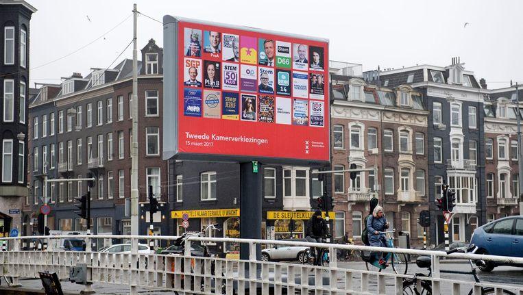 Op Westeinde wordt een verkiezingsbord geplaatst met verkiezingsposters van alle partijen die deelnemen aan de Tweede Kamerverkiezingen. Beeld ANP