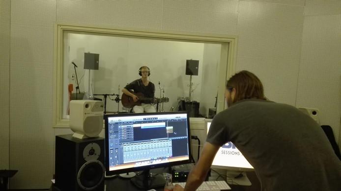 Jeroen Stoot van There There op de akoestische gitaar in de studio van A-Broad.