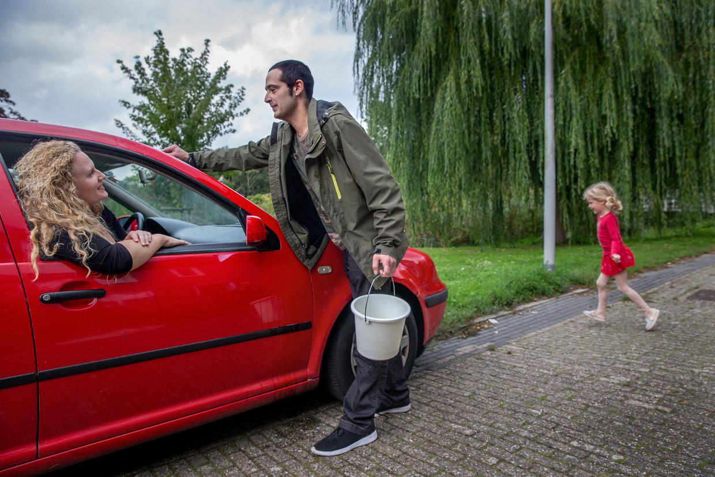 Ingrid Kamerling zit in de auto, terwijl haar neef Chris Verhoeff de ruit wast. Verhoef was de mantelzorger van hun oma, en nam haar nog een keer meer op vakantie in deze rode auto van zijn opa.