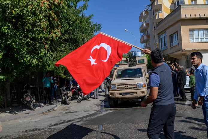 Een man wuift met de Turkse vlag als eenheden van het Turkse leger de Syrische provincie Sanliurfa binnengaan.