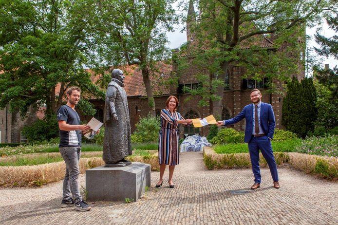 Museum Prinsenhof-directeur Janelle Moerman overhandigt wethouder Bas Vollebregt (r.) en ondernemer Jon Cornelese bij het standbeeld van Willem van Oranje op het Agathaplein een exemplaar van de nieuwe historische stadswandeling.