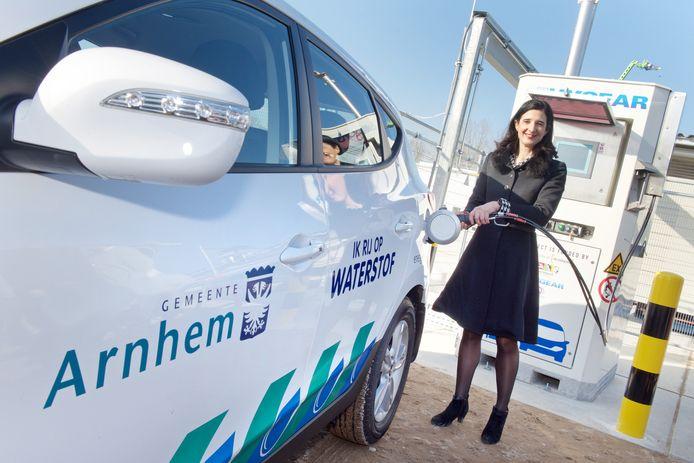 Toenmalig wethouder Anja Haga tankt een auto van de gemeente vol met waterstofgas kort na de opening van het waterstofgaspompstation op de Kleefse Waard in Arnhem.