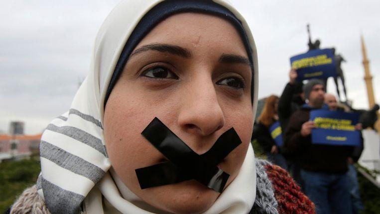 Een vrouw protesteert tegen de opsluiting van journalisten in Egypte. Beeld REUTERS