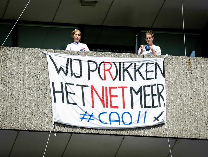 Medewerkers van het Onze Lieve Vrouwe Gasthuis in Amsterdam protesteren voor de ingang van het ziekenhuis.