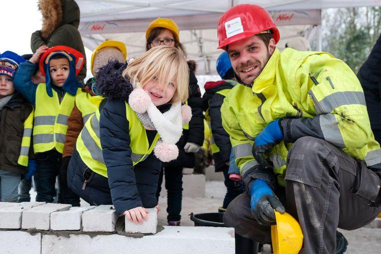 De kleuters leggen de eerste steen van hun nieuwe schoolgebouw.