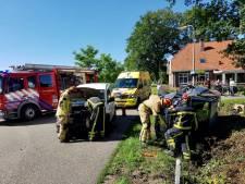 Frontale botsing in Mander: Auto op zijn kant en twee gewonden