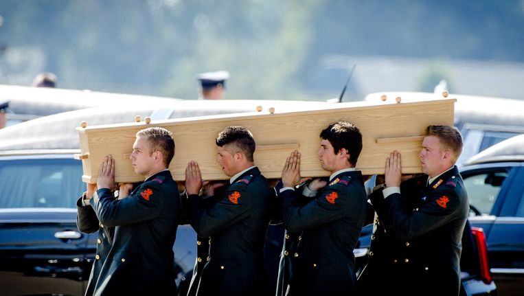 Militairen dragen op de dag van nationale rouw kisten met de slachtoffers van MH17 naar de lijkwagens. Beeld anp
