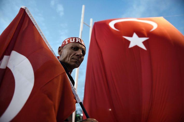 Een aanhanger van Erdogan met een Turkse vlag. Beeld afp