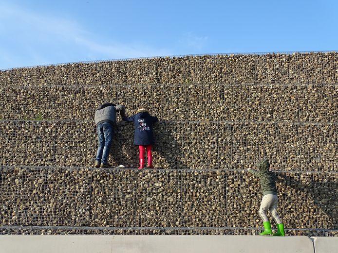 Kinderen zoeken in de schanskorven langs de nieuwe N34 naar door henzelf of klasgenoten versierde keien.