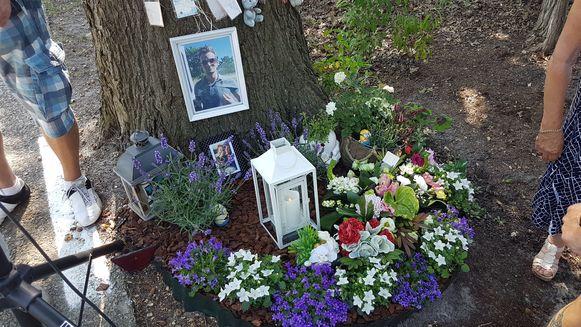 Op de plaats van het ongeval liggen nog altijd bloemen, hangen foto's aan de boom.