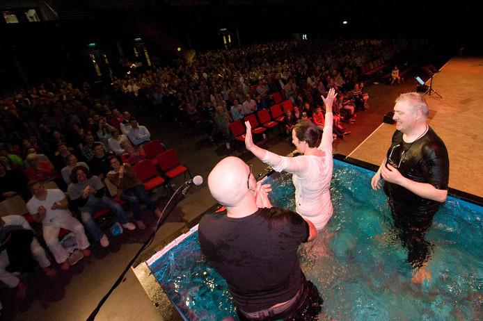 Kerkgangers laten zich kopje onder duwen in een grote bak water op het podium van Mozaiek0318 in Veenendaal. Deze 'megakerk' overweegt zich ook in Apeldoorn te vestige