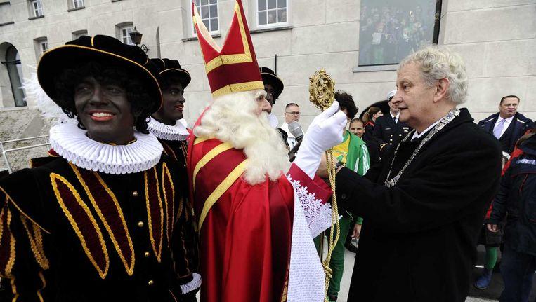 Burgemeester Eberhard van der Laan (R) verwelkomt Sinterklaas en zijn pieten bij de intocht in Amsterdam, vorig jaar december. Beeld anp