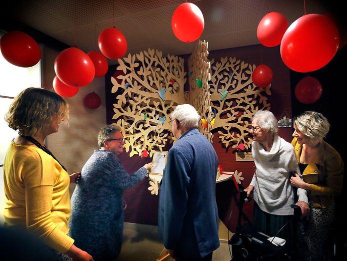 Activiteitenbegeleider Anke Zondag (links) ziet erop toe dat Belia den Hartog een wens in de nieuwe wensboom van Huis ter Leede hangt.