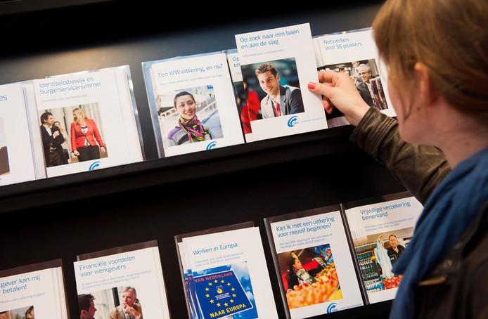 Een werkzoekende bekijkt folders bij het UWV Werkplein.